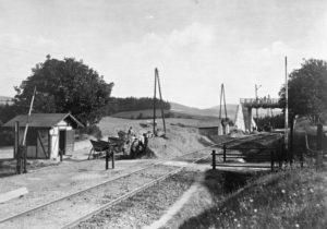 Stavba nadjezdného mostu v km 125,738 cesty z Opřetic do Božkovic v rámci stavby II.koleje v úseku Votice-město - Benešov, realizované v letech 1919-24. V popředí služební domek závorářského stanoviště a původní úrovňový přejezd se závorami výše zmíněné cesty.